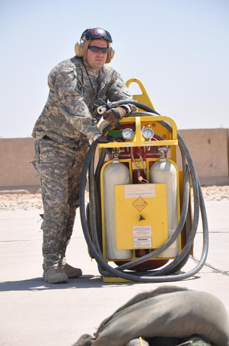 Ohio National Guard Spc. Thomas Masters, of Galloway, Ohio, and an aircraft refueler with Company E, stands guard next to fire extinguishers while a UH-60 Black Hawk helicopter is being refueled on Monday, August 24, 2009.