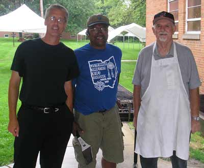 Father Chris helps cook burgers at Christ the King picnic