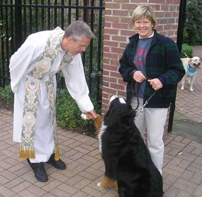 Father Chris Weber greets Joan Atkian's dog Hub