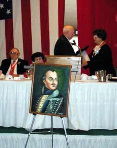 Mercedes Karpinski Spotts receiving award with Pulaski painting in front