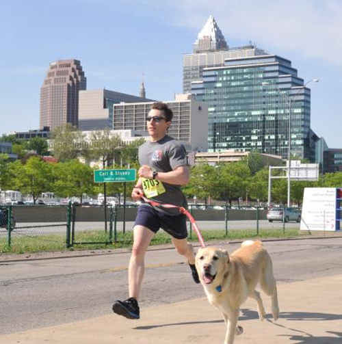 Lt. Timothy Jones, a member of Coast Guard Marine Safety Unit Cleveland, runs with Sam, a golden retriever