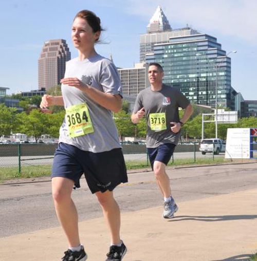 Seaman Sarah Molli, a member of Coast Guard Station Ashtabula, Ohio, and Master Chief Jeffrey Waters, a member of Coast Guard Base Cleveland, participate in the Run to Remember event held in Cleveland, May 17, 2013. In the event honoring those who have died saving lives, Molli placed first in her age group and first for females overall.