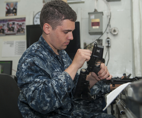 Aviation Ordnanceman Airman Curt Wozniak, from Cleveland, Ohio, cleans an M4 rifle in the ship's armory aboard aircraft carrier USS Carl Vinson (CVN 70). Carl Vinson is pierside at Naval Air Station North Island. (U.S. Navy photo by Mass Communication Specialist 3rd Class Scott Fenaroli/Released)