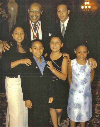 Louis Stokes receiving Congressional Distinguished Service Medal, with Eric Hammond (grandson), and front row from left grandchildren Alexandra Thompson, Grand Hammond, Nicolette Thompson, and cousin Dacia Johnson
