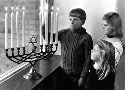 Rabbi Fred Eisenberg's children light the Menorah in 1968