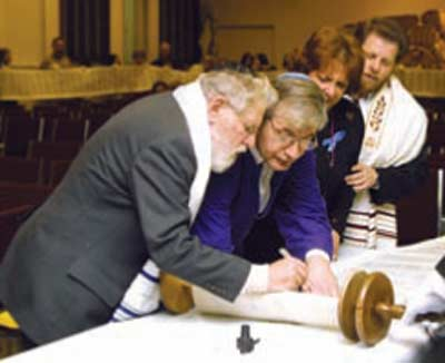 Rabbi Fred Eisenberg inscribes a letter  in Temple Israel Ner Tamid's new Torah